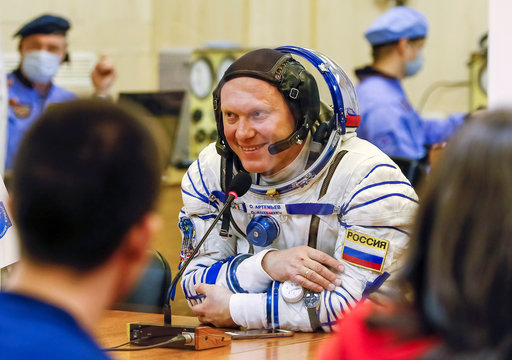 The International Space Station (ISS) crew member Oleg Artemyev of Russia smile as he talks with his family shortly before the launch at the Baikonur Cosmodrome