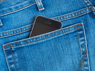 Black mobile phone with a camera in the back pocket of blue jeans