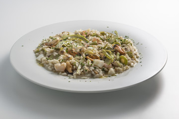 Round white dish of risotto with artichokes and seafood