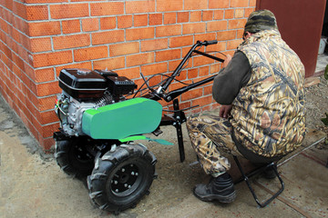 a man sits and prepares a green motor-cultivator with a gasoline engine to work. Repair and service. red brick wall in the background. Copy space for text