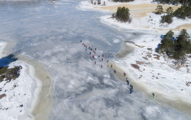 Aerial view of frozen sea. People are skating on the ice.