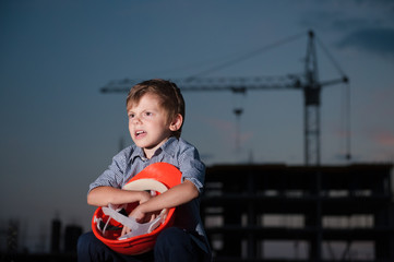 screaming little boy sitting with orange helmet in his hands on background of construction site with crane at dusk