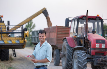 Farmer in front of tractor and combine harvester during harvest