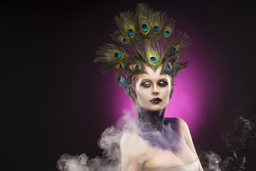 Beautiful big breast girl wearing peacock feathers in her hair and artistic violet shiny body art on her neck, vanguard makeup in theatrical smoke.