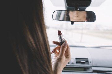 Brunette executive woman inside the car is painting her lips.