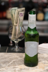 Generic beer bottle with blank label served by bartender waiting for customer to drink alcohol. Dollar bill money sits in brandy glass in background containing tips for restaurant server