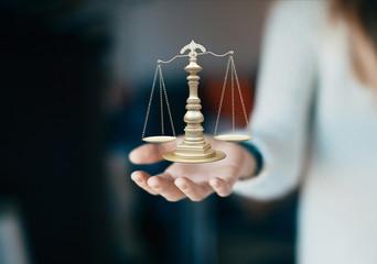 Mano con bilancia, tribunale e giustizia