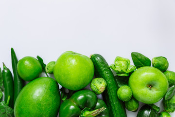 green fruits and vegetables on white background with copy space on top