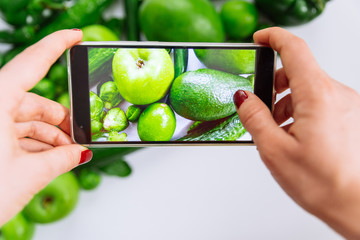 woman take picture of green vegetables and fruits on her phone. cucumber apple mango lime on white background