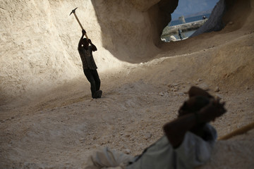 A man uses a pick to break rocks and get sand in a sand mine on the outskirts of Fond Parisien