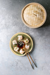 Asian steam potstickers dumplings stuffed by shrimps, served on ceramic plate with soy sesame sauce, chopsticks, bamboo steamer over grey texture background. Top view, copy space.
