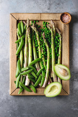 Variety of raw uncooked organic young green vegetables asparagus, peas, pod pea, avocado in wooden tray over grey texture background. Top view, space. Healthy eating
