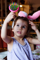 Little kid girl having fun with bunny ears on head at easter day.