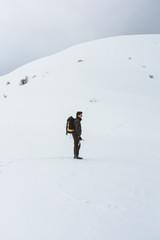 Tourist walking on snowy mountain