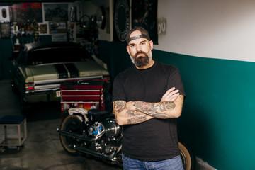 Tattooed mechanic in garage