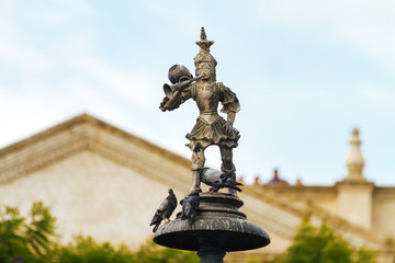Close up of statue of Tuturutu (Elf with trumpet) with pigeons in the Plaza de Armas