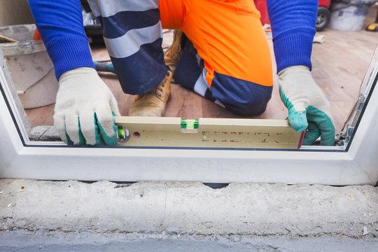 worker installs plastic windows and doors