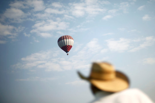 A hot air balloon floats above of a man walking to climbs the Pyramid of the Sun and welcome the spring equinox in the pre-hispanic city of Teotihuacan on the outskirts of Mexico City