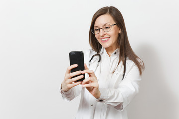 Smiling fun beautiful young doctor woman with stethoscope, glasses isolated on white background. Female doctor in medical gown doing selfie on mobile phone. Healthcare personnel, health, medicine.
