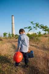 sad little caucasian boy with helmet and tool case in hands walking towards factory with pipe