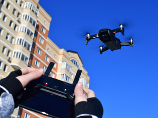 Quadrocopter flies in sky and hands with a control panel