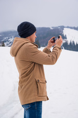 A young man takes a picture of a mountain landscape on a cellphone in Transcarpathia.