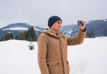 A young guy takes a picture of a mountain landscape on a cellphone in Transcarpathia.