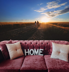Soft home sofa in the background of the landscape with people walking away into the field. The concept of downshift. In harmony with nature. Honeymoon.