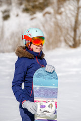 Portrait of smiling sportswoman in helmet with snowboard in winter day