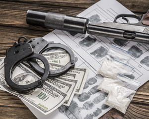 Drugs and money, a pistol with a silencer and handcuffs on a wooden table. Sale of drugs. International crime, human trafficking. control, illicit trafficking in narcotic substances.