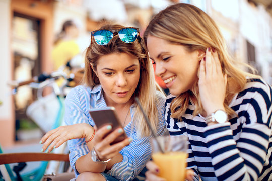 Two young women online via a smartphone in cafe