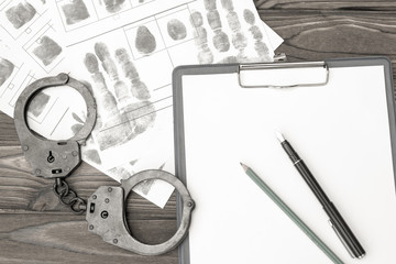 handcuffs with fingerprints on a wooden background. arrest. detention of a criminal.
