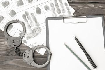 handcuffs with fingerprints on a wooden background. arrest. detention of a criminal.