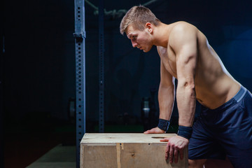 Portrait of fatigued fitness guy. Near the wooden cube. Cross fit style.