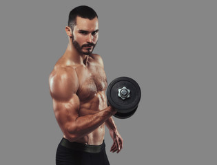Brutal athletic bearded shirtless male doing exercise with dumbb