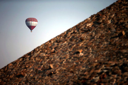 Hot air balloon floats above the Pyramid of the Sun during the spring equinox in the pre-hispanic city of Teotihuacan on the outskirts of Mexico City