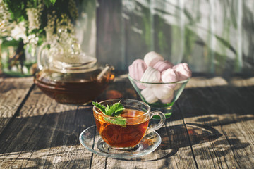 Delicious strawberry green mint tea in a transparent glass teapot and Cup in the summer, on a rustic wooden table with marshmallows. Copy spase