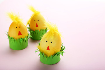 Yellow eggs with funny chicken faces on pink background