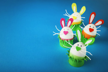 Eggs with funny rabbit faces on blue background