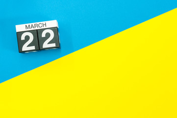 March 22nd. Day 22 of march month, calendar on blue and yellow background flat lay, top view. Spring time. Empty space for text