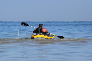 Garden Poster Water Motor sports Man rowing in inflatable kayak in the sea.