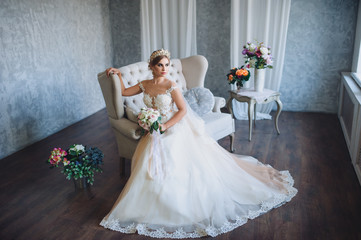 A beautiful bride in a lace dress sits in an armchair with a bouquet in her hands. Fashion. Valuable jewellery. Interior