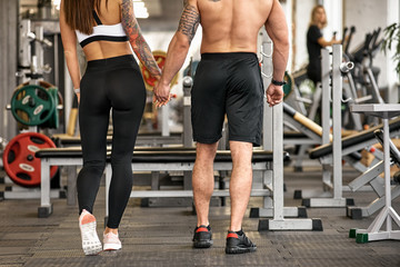 Back view of two young lovers in modern gym