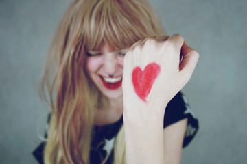 Chica joven con un corazón rojo pintado en su mano