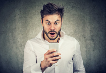 Surprised young man watching smartphone