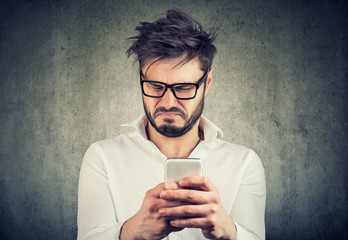 Exasperated man watching phone looking disgusted