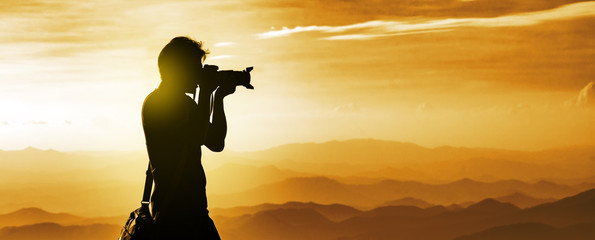 Silhouette of a backpacker photographer with mountains layer background during the sunset Fotobehang