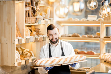 Handsome seller in uniform holding a big loaf of bread in the store with bakery products