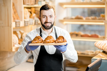 Portrait of a handsome seller in uniform standing with delicious croissants in the store with bakery products