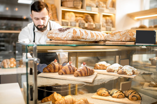 Seller putting delicious croissants on the store showcase of the bakery house
